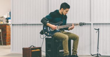 A man practicing the guitar with a guitar amp